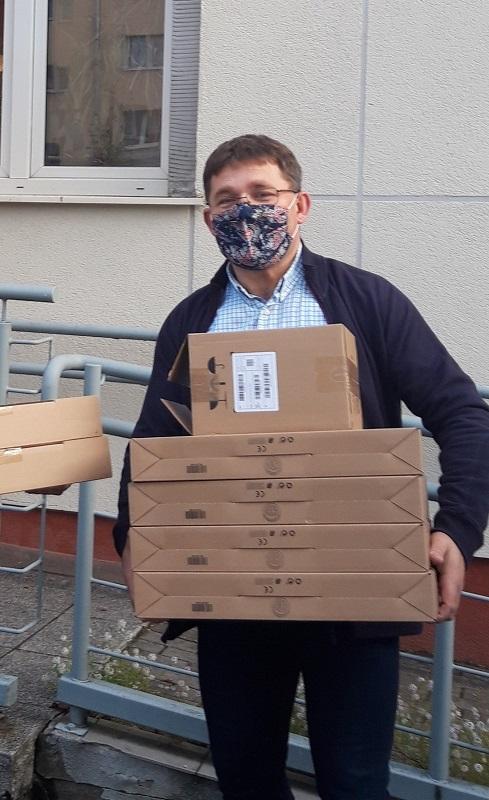 """Zdjęcie: Piotr Wróblewski, dyrektor """"Domów dla Dzieci"""" Gdańskiej Fundacji Innowacji Społecznej z przekazanymi laptopami."""